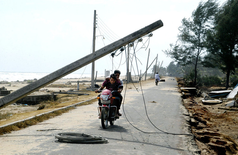 . Sri Lankan motorcyclists duck under a fallen telegraph pole as they ride along the coastal road in the devastated town of Valachchenai, some 180 kms north-east of Colombo, 28 December 2004.  The tsunami which struck Sri Lanka 26 December, lashed more than three quarters of the island\'s coastline, leaving at least 17,800 people dead and tens of thousands homeless. The authorities stepped up appeals for relief supplies to treat tens of thousands of people wounded by huge waves and falling debris. STR/AFP/Getty Images