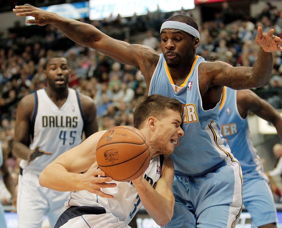 . Dallas Mavericks guard Gal Mekel (33) loses control of the ball as he runs into Denver Nuggets\' Ty Lawson (3) during the second half of an NBA basketball game Monday, Nov. 25, 2013, in Dallas. Denver won 110-96. (AP Photo/Brandon Wade)