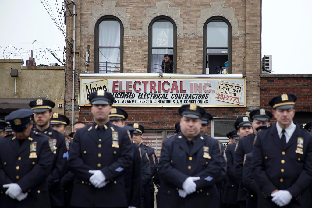 . A spectator looks out onto officers during the funeral of New York Police Department Officer Wenjian Liu at Aievoli Funeral Home, Sunday, Jan. 4, 2015, in the Brooklyn borough of New York. Liu and his partner, officer Rafael Ramos, were killed Dec. 20 as they sat in their patrol car on a Brooklyn street. The shooter, Ismaaiyl Brinsley, later killed himself. (AP Photo/John Minchillo)