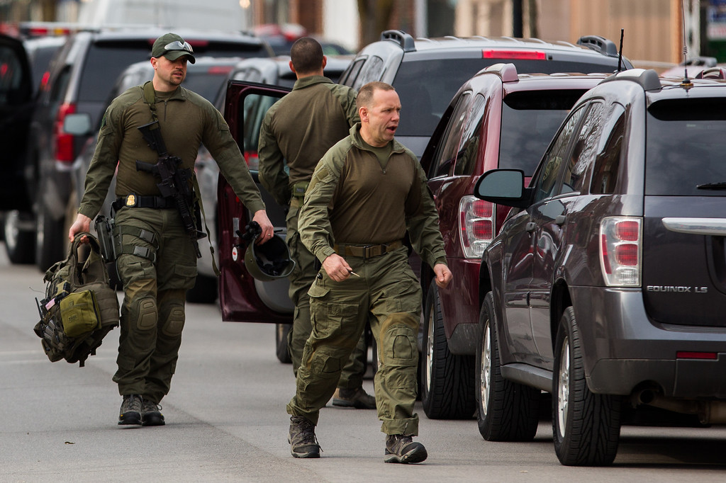 . Tactical police officers return to their vehicles on North Main Street, equipment in hand, after waiting at the scene of a standoff with a murder suspect on March 13, 2013 in Herkimer, New York. (Photo by Brett Carlsen/Getty Images)