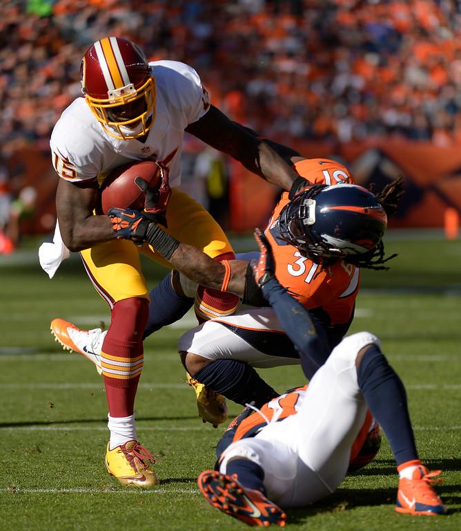 . Washington Redskins wide receiver Josh Morgan (15) shakes off a tackle by Denver Broncos cornerback Omar Bolden (31) in the second quarter.   (Photo by Joe Amon/The Denver Post)