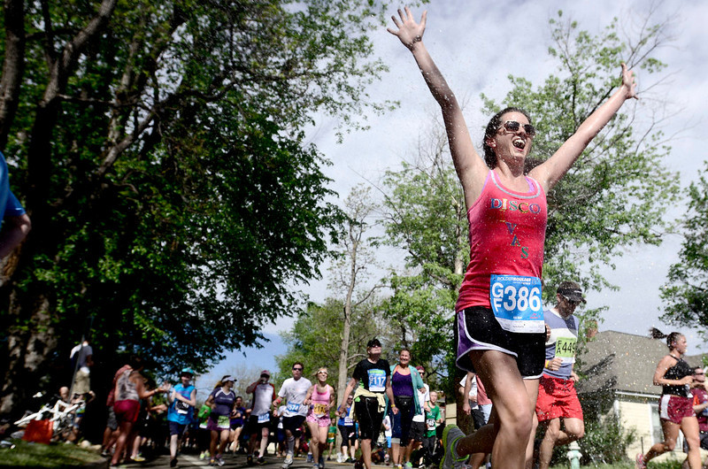 . Melissa Ricksecker raises her hands and cheers as she runs through a spray of water during the Bolder Boulder in Boulder, Colorado May 27, 2014.  DAILY CAMERA/ Mark Leffingwell