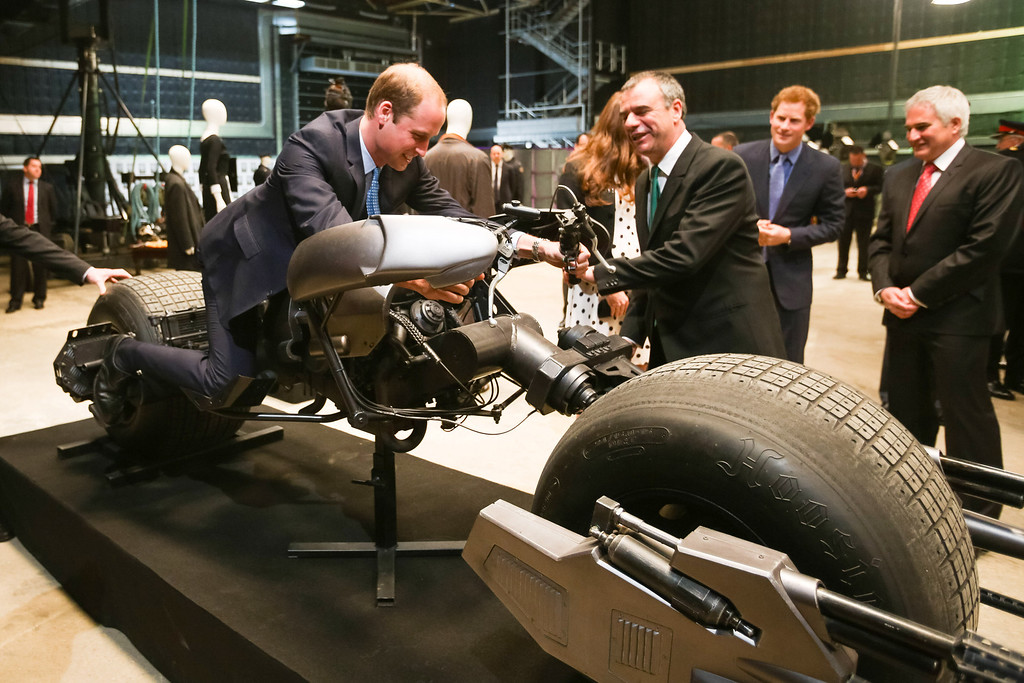 . Prince William, Duke of Cambridge site the \'Batpod\', which was used in the Batman films as Catherine, Duchess of Cambridge and Prince Harry look on during the Inauguration Of Warner Bros. Studios Leavesden on April 26, 2013 in London, England.  (Photo by Paul Rogers - WPA Pool/Getty Images)