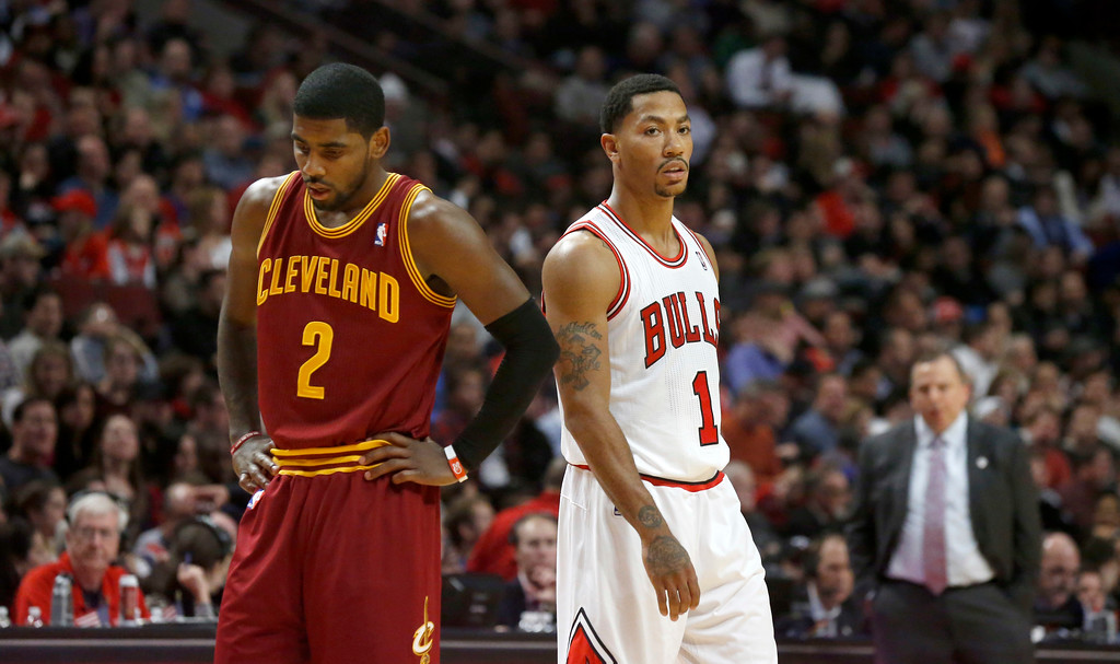 . Chicago Bulls point guard Derrick Rose (1) and Cleveland Cavaliers point guard Kyrie Irving wait for a Bulls free throw attempt during the second half of an NBA basketball game against the Chicago Bulls Monday, Nov. 11, 2013, in Chicago. The Bulls won 96-81. (AP Photo/Charles Rex Arbogast)