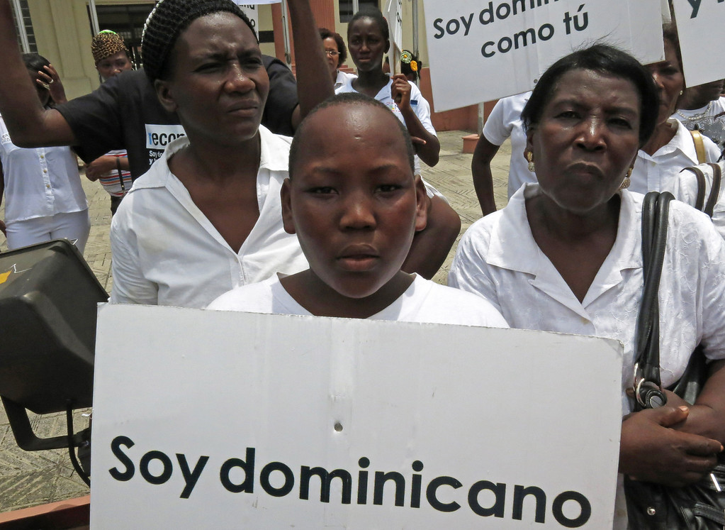 ". FILE - In this Aug. 12, 2013 file photo, a youth of Haitian descent holds a sign that reads in Spanish ""I\'m Dominican\"" during a protest demanding that President Danilo Medina stop the process to invalidate their birth certificates after authorities retained their ID cards, in Santo Domingo, Dominican Republic. The Dominican Republic\'s top court on Thursday, Sept. 26, 2013 stripped citizenship from thousands of people born to migrants who came illegally, a category that overwhelmingly includes Haitians brought in to work on farms. The decision cannot be appealed, and it affects all those born since 1929. (AP Photo/Ezequiel Abiu Lopez, File)"