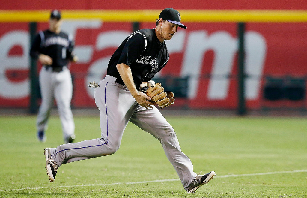 . Colorado Rockies\' DJ LeMahieu, right, bobbles the ball but make the catch on a foul ball hit by Arizona Diamondbacks\' Alfredo Marte as Rockies\' Brandon Barnes, left, looks on during the eighth inning of a baseball game Sunday, Aug. 31, 2014, in Phoenix. The Diamondbacks defeated the Rockies 6-2. (AP Photo/Ross D. Franklin)