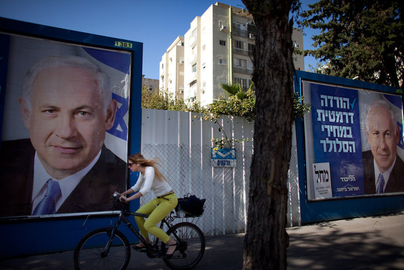 . An Israeli woman rides her bicycle past posters of Israeli Prime Minister Benjamin Netanyahu on January 21, 2013 in Tel Aviv, Israel. Israeli elections are scheduled for January 22 and so far showing a majority for the Israeli right. (Photo by Uriel Sinai/Getty Images)