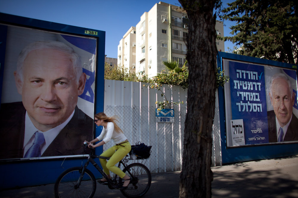Description of . An Israeli woman rides her bicycle past posters of Israeli Prime Minister Benjamin Netanyahu on January 21, 2013 in Tel Aviv, Israel. Israeli elections are scheduled for January 22 and so far showing a majority for the Israeli right. (Photo by Uriel Sinai/Getty Images)