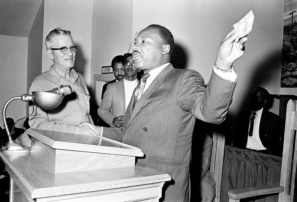 """. Dr. Martin Luther King Jr. (right) who is visiting Mississippi to drum up funds his Poor Peoples March 19, 1968 in Marks, Mississippi USA.  King holds a crisp $100 bill and listens to remarks by a  Marks, Mississippi, resident , at left, who identified himself as W.B. \""""Money\"""" Mobley.   Mr Mobley pushed his way through a crowd of several hundred and interrupted King\'s speech to present the $100 donation and asked for the floor.     Dr. King obliged. (AP Photo/Jack Thornell)"""