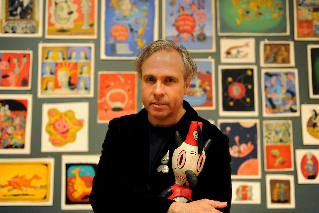 """. Gary Baseman with Toby in the office of the exhibition \""""Gary Baseman: The Door is Always Open,\"""" at the Skirball Cultural Center, Wednesday, April 24, 2013. Baseman\'s work is known for his vibrant, cartoon-like, artistic style in publications such as The New Yorker, Rolling Stone and the LA Times. He designed for the game Cranium and created the animated TV series, Teacher�s Pet.The exhibition design is based on his childhood home in LA�s Fairfax district and includes family furniture and snapshots and many items of interior décor designed by the artist, including wallpaper, pillows, a chandelier and more. (Michael Owen Baker/Staff Photographer)"""