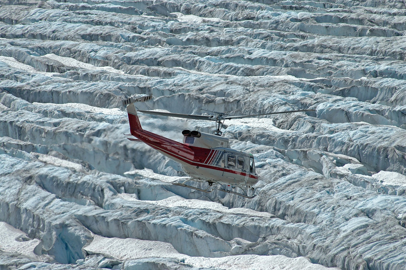 Bell 212 flying closely over seracs on the Conrad Icefield
