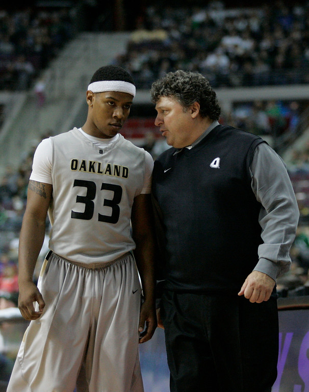 . Oakland coach Greg Kampe talks to guard Ryan Bass (33) after being pulled from the NCAA college basketball game against Michigan State in the second half Saturday, Dec. 11, 2010, in Ann Arbor, Mich. (AP Photo/Duane Burleson)