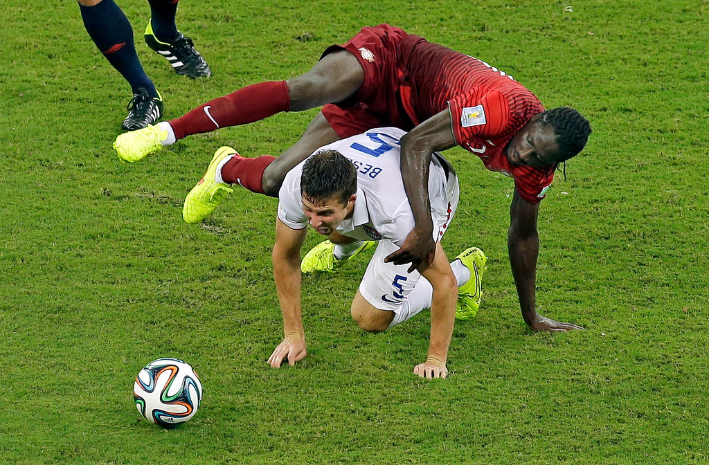 . United States\' Matt Besler, bottom, and Portugal\'s Eder challenge for the ball during the group G World Cup soccer match between the USA and Portugal at the Arena da Amazonia in Manaus, Brazil, Sunday, June 22, 2014. (AP Photo/Themba Hadebe)