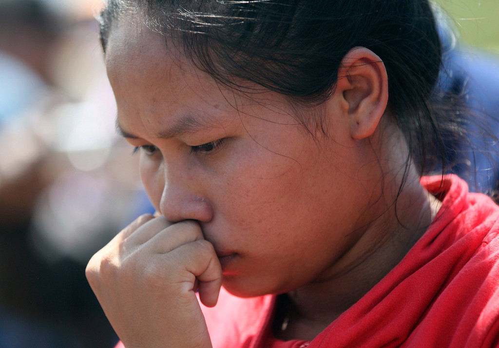 . A woman looks at debris scattered on the riverbank where a Lao Airlines turboprop plane apparently hit hard before skidding into the water and sinking Wednesday, in Pakse, Laos on Thursday, Oct. 17, 2013.  (AP Photo/Sakchai Lalit)