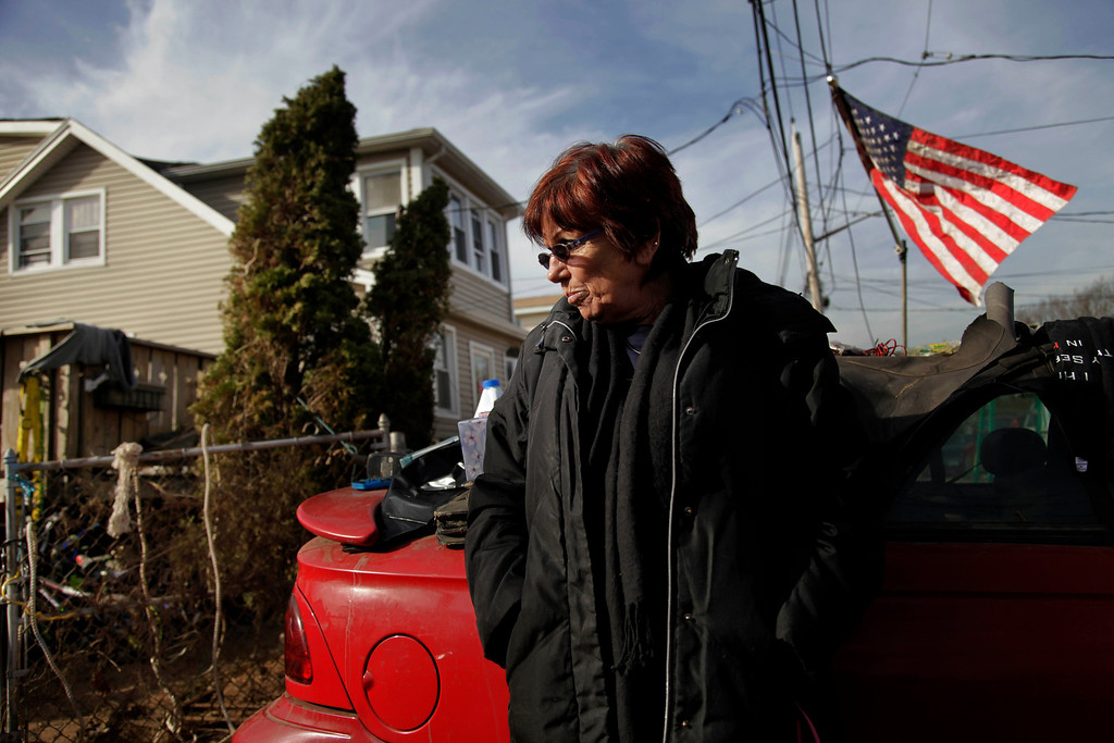 """. FILE - In this Nov. 20, 2012 file photo, Marge Gatti stands in front of her home, which was damaged by Superstorm Sandy, in the Midland Beach section of the Staten Island borough of New York. Six months after the storm, Gatti, the matriarch of her family, said \""""The whole family\'s separated, and it\'s terrible, you know?\"""" The flood-soaked place was demolished months ago, and they\'re waiting for a government buyout. Now the family is scattered across New Jersey, New York and Texas.   (AP Photo/Seth Wenig, File)"""