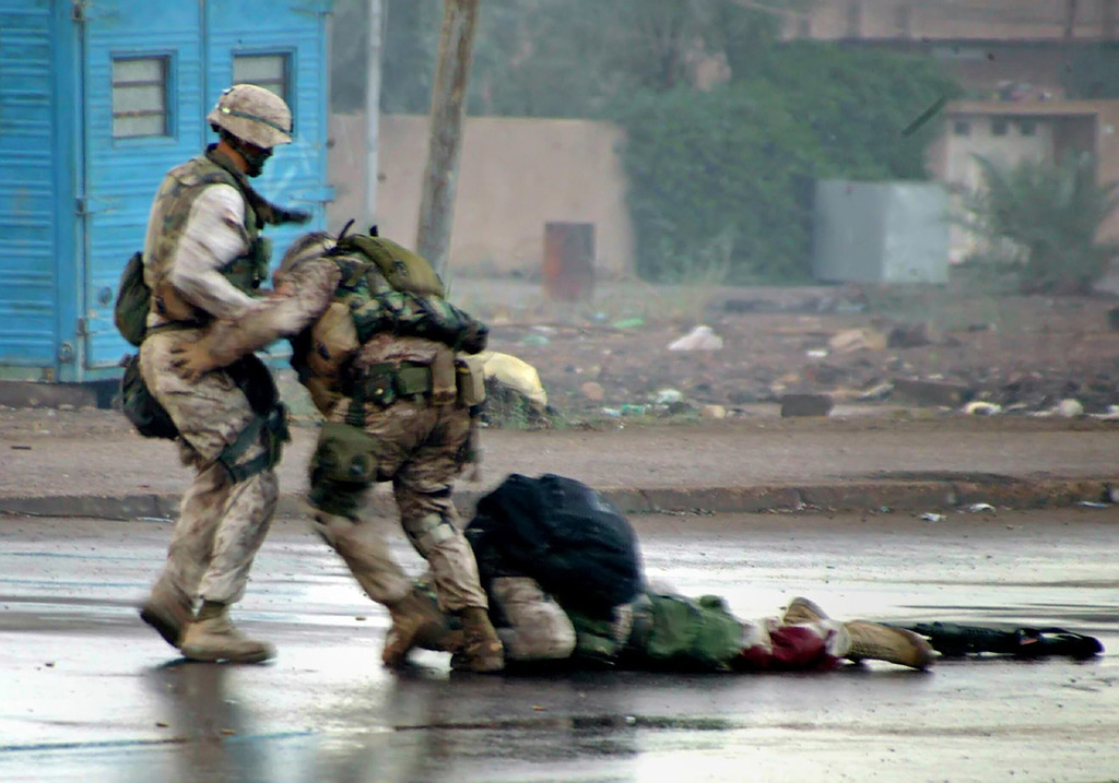 . U.S. Marine platoon Gunnery Sergeant, Ryan P. Shane (C), from the 1st Battalion of the 8th Marine Regiment and another member of 1/8 pull a fatally wounded comrade to safety while under fire during a military operation in the Iraqi western city of Falluja, in this photograph released on December 17, 2004. Seconds later Sgt. Shane was also injured by nearby enemy fire, U.S. Marine officer said. REUTERS/HO/USMC/Cpl. Joel A. Chaverri
