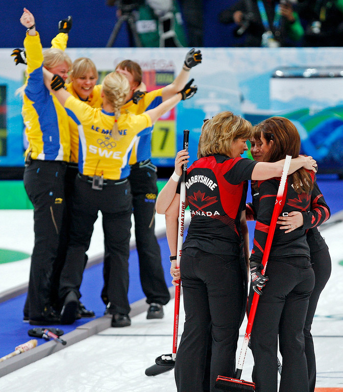 . Canada\'s skip Cheryl Bernard, right, is consoled as Sweden celebrates after the gold medal women\'s curling match at the Vancouver 2010 Olympics in Vancouver, British Columbia, Friday, Feb. 26, 2010. (AP Photo/Morry Gash)