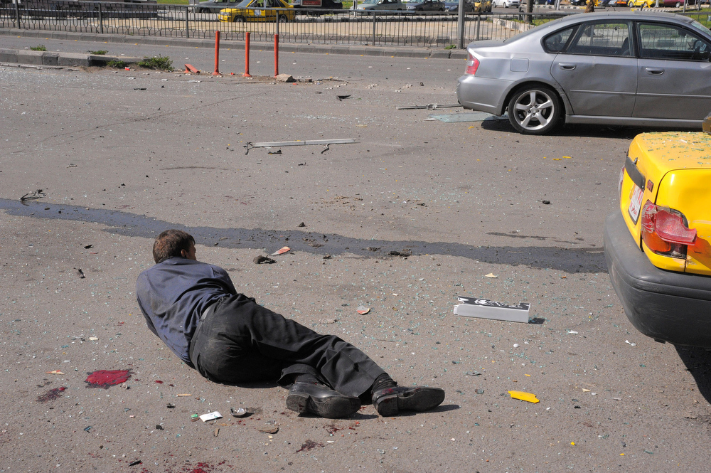 Description of . This photo released by the Syrian official news agency SANA shows an injured Syrian man lying on the ground after a huge explosion that shook central Damascus, Syria, Thursday, Feb. 21, 2013. A car bomb shook central Damascus on Thursday, exploding near the headquarters of the ruling Baath party and the Russian Embassy, eyewitnesses and opposition activists said. (AP Photo/SANA)