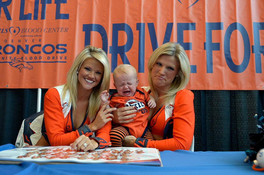 . DENVER, CO - OCTOBER 22: Gaige Thayen 9 mos old cries as he is held by Cheerleaders Kendal (L) and Tristan (R) during a photo op at The Denver Broncos and Bonfils Blood Center\'s 16th annual Drive for Life community blood drive October 22, 2013 at Sports Authority Field. (Photo by John Leyba/The Denver Post)