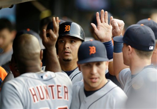 . Detroit Tigers\' Victor Martinez is congratulated by teammates after scoring after a bases-loaded walk by Alex Avila in the second inning of a baseball game Cleveland Indians Tuesday, Sept. 2, 2014, in Cleveland. (AP Photo/Tony Dejak)