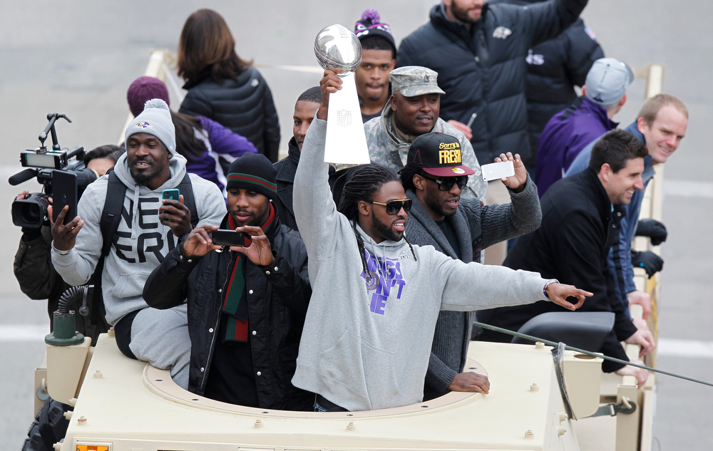 Description of . Wide receiver Torrey Smith of the Super Bowl champion Baltimore Ravens, hoists the Vince Lombardi trophy as he and his teammates take part in the Ravens victory parade in Baltimore, Maryland on February 5, 2013. The Ravens defeated the San Francisco 49's 34-31 to win the NFL Championship in New Orleans, on February 3, 2013.  MOLLY RILEY/AFP/Getty Images