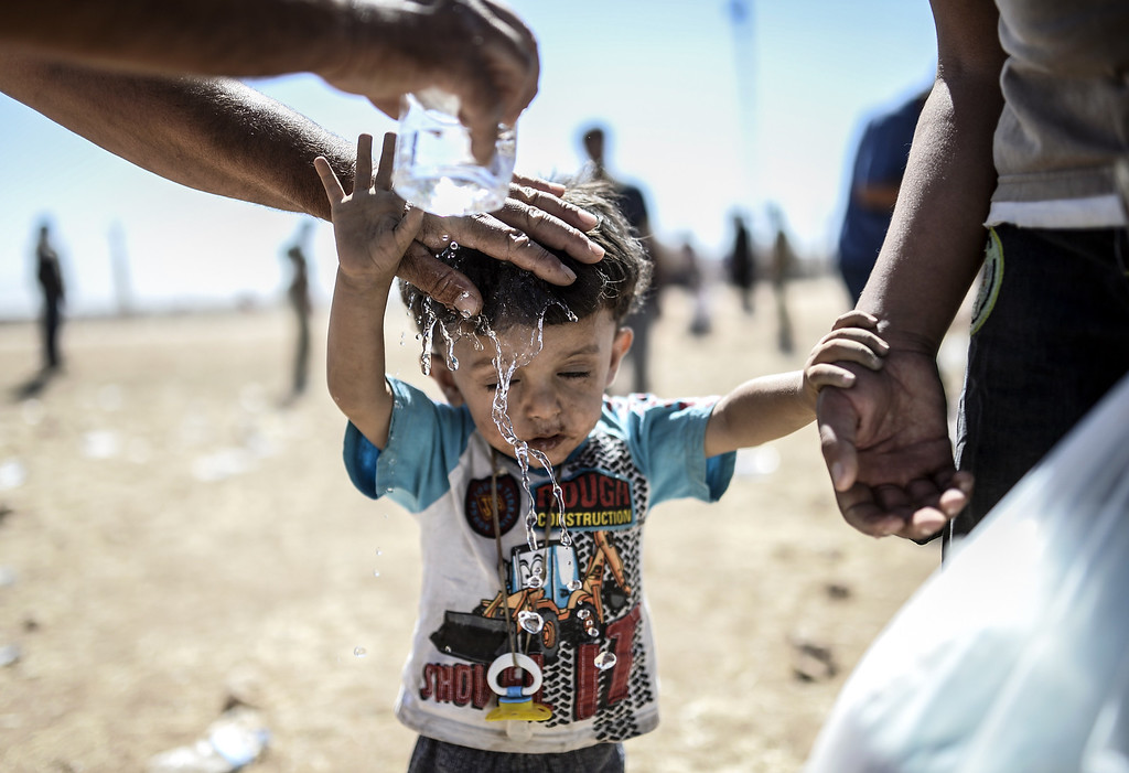 ". A Syrian Kurd pours water on a child after they crossed the border between Syria andTurkey near the southeastern town of Suruc in Sanliurfa province, on September 20, 2014. Several thousand Syrian Kurds began crossing into Turkey on September 19 fleeing Islamic State fighters who advanced into their villages, prompting warnings of massacres from Kurdish leaders. Turkey on September 19 reopened its border with Syria to Kurds fleeing Islamic State (IS) militants, saying a ""worst-case scenario\"" could drive as many as 100,000 more refugees into the country. BULENT KILIC/AFP/Getty Images"