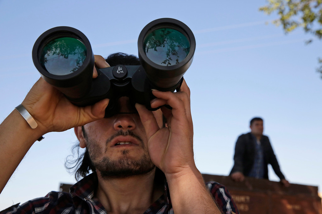 . In this Monday, Oct. 6, 2014 file photo, a Turkish Kurd, standing on the  the Turkey-Syria border, uses binoculars to watch fighting between militants of the Islamic State group and Kurdish forces in Kobani, Syria, on outskirts of Suruc, Turkey.    (AP Photo/Lefteris Pitarakis< File)