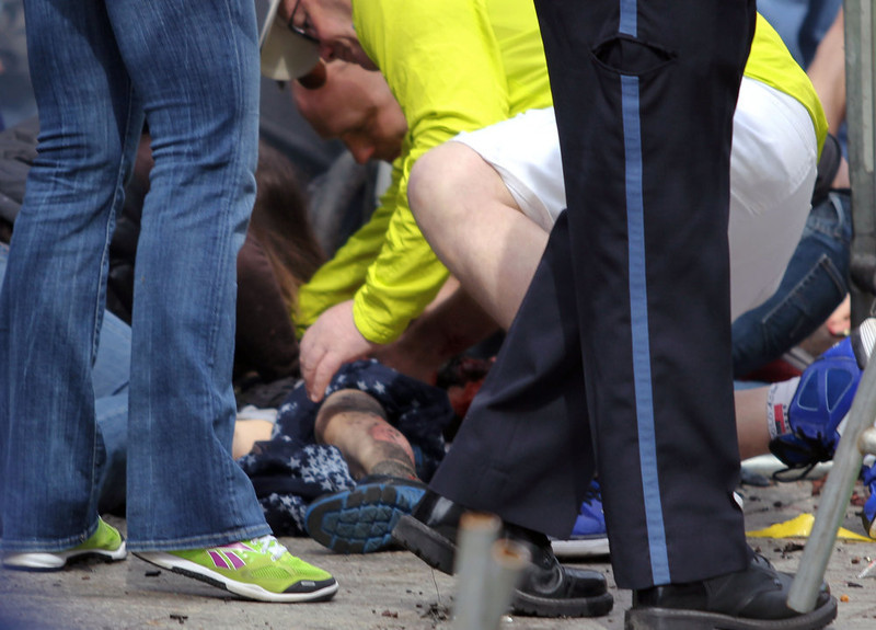 . In this photo provided by The Daily Free Press and Kenshin Okubo, people help an injured person after an explosion at the 2013 Boston Marathon in Boston, Monday, April 15, 2013. Two explosions shattered the euphoria of the Boston Marathon finish line on Monday, sending authorities out on the course to carry off the injured while the stragglers were rerouted away from the smoking site of the blasts. (AP Photo/The Daily Free Press, Kenshin Okubo)