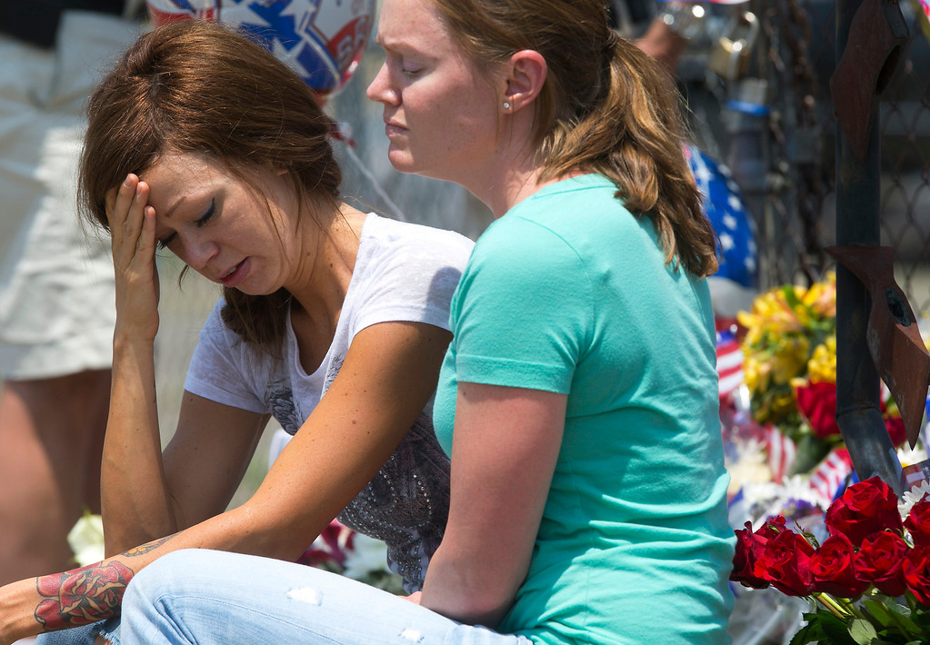 . Juliann Ashcraft, left, of Prescott, the wife of Andrew Ashcraft, who was killed battling the Yarnell Hill Fire reacts as she sits by a memorial for the fallen firefighters in front of Prescott Fire Station #7 on Monday, July 1, 2013.  (AP Photo/The Arizona Republic, David Wallace)
