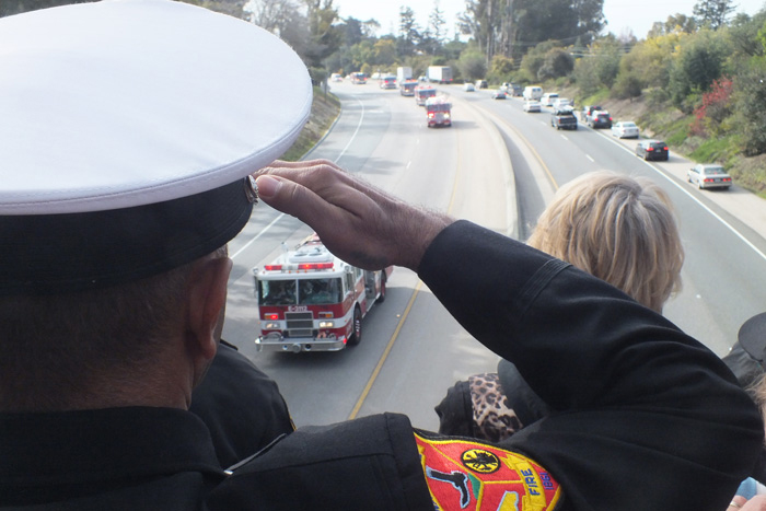 ". A Watsonville fireman salutes the funeral procession for Elizabeth Butler and Loran ""Butch\"" Baker from the Pasatiempo overpass at Highway 17. Memorial services were held at HP Pavilion in San Jose, Calif."