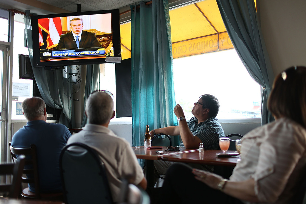 . People  listen as Puerto Rican Governor Alejandro Garcia Padilla addresses the island\'s residents in a televised broadcast regarding the governments $73 billion debt on June 29, 2015 in San Juan, Puerto Rico.  The governor said that the people on the island will have to sacrifice and share in the responsibilities for pulling the island out of debt.  (Photo by Joe Raedle/Getty Images)