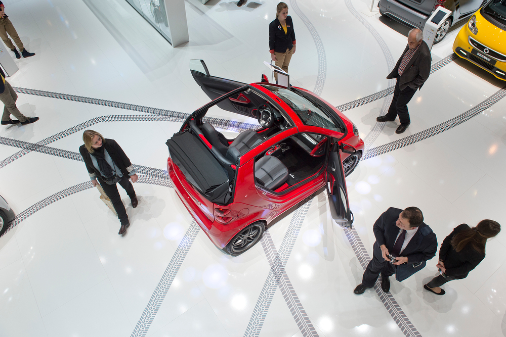 Description of . People stand around a Smart car in the Smart booth during the press day at the 84th Geneva International Motor Show in Geneva, Switzerland, Wednesday, March 5, 2014. (AP Photo/Keystone, Sandro Campardo)