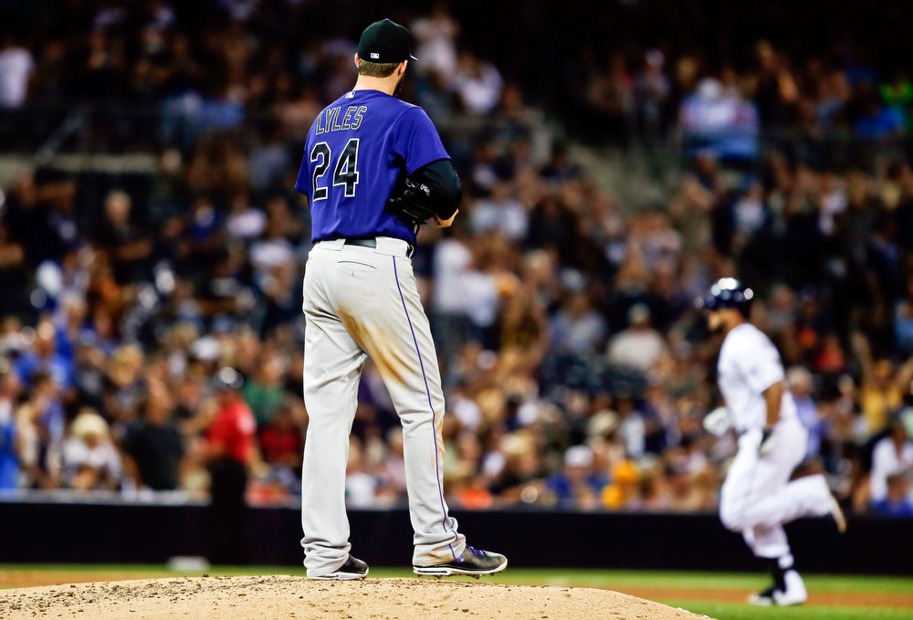 . Colorado Rockies starting pitcher Jordan Lyles runs up a new ball as he watches San Diego Padres\' Yonder Alonso round the bases with a solo home run in the fourth inning of a baseball game Monday, Aug. 11, 2014, in San Diego. (AP Photo/Lenny Ignelzi)