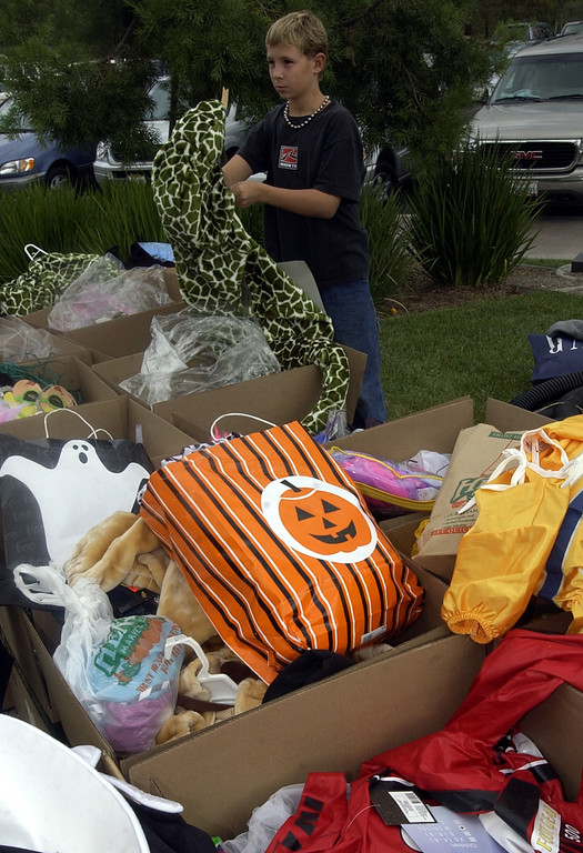 . Brandon Worley, whose home was lost in the Cedar Fire in San Diego picks through donated Halloween costumes at St. Gregory\'s Church in the Scripps Ranch arera of San Diego, Calif. Friday  Oct. 31, 2003. (AP Photo/Lenny Ignelzi)