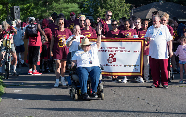 07/26/18 Wesley Bunnell | Staff Participants in the eleventh annual Walk & Roll at Walnut Hill Park begin their lap around the park on Thursday evening. Holding the banner are Commissioners Alicia Rostowski, L, and Alden Russell, R, with the city's Commission on Persons with Disabilities who hosted the event. The Walk and Roll celebrates the signing of the American with Disabilities Act of 1980 as well as raises awareness of abilities people with disabilities still have.