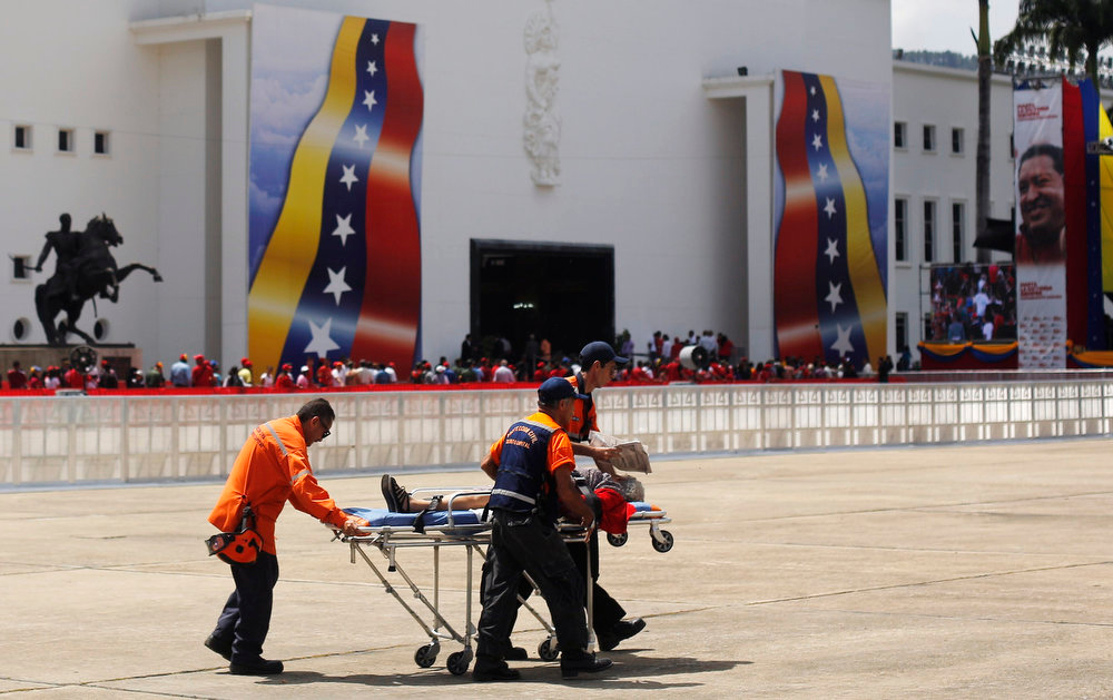 . Medics carry away a supporter of Venezuela\'s late President Hugo Chavez who fainted while waiting in line with thousands of others to view his body in state at the Military Academy in Caracas on March 7, 2013. Venezuelans flocked to pay tribute to Chavez two days after he died of cancer.     REUTERS/Tomas Bravo