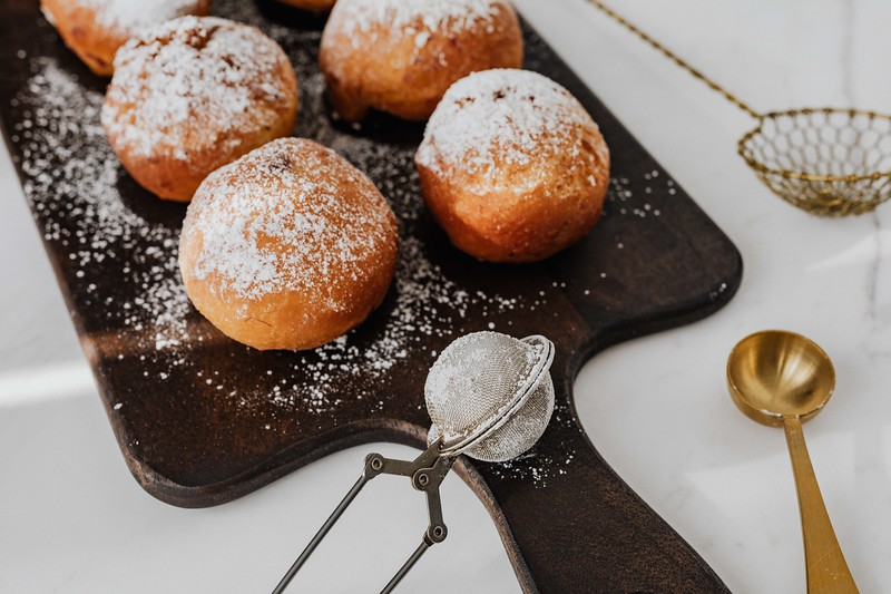 kaboompics_Homemade doughnuts covered with powdered sugar. Traditional speciality on Fat Thursday in Poland..jpg