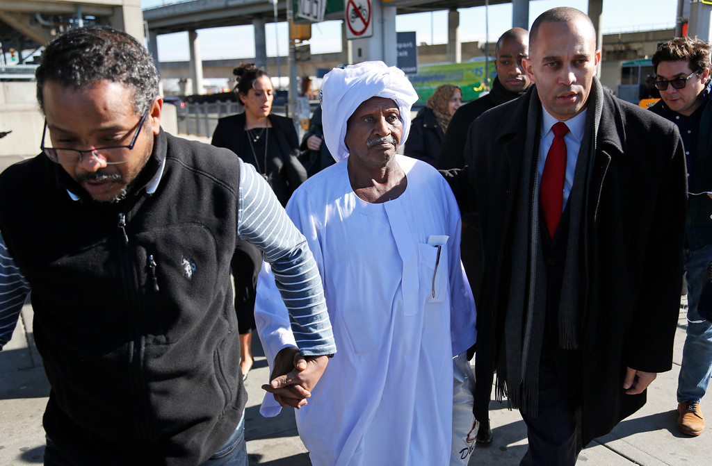 . Yassin Abdelrhman, center, of Sudan, is escorted out of John F. Kennedy Airport by his son, Ali Suliman, left, and Congressman Hakeem Jeffries, in New York, Sunday, Jan. 29, 2017. Attorneys advocating on his behalf said he is a lawful permanent resident and was held at the airport for more than 24 hours. (AP Photo/Seth Wenig)