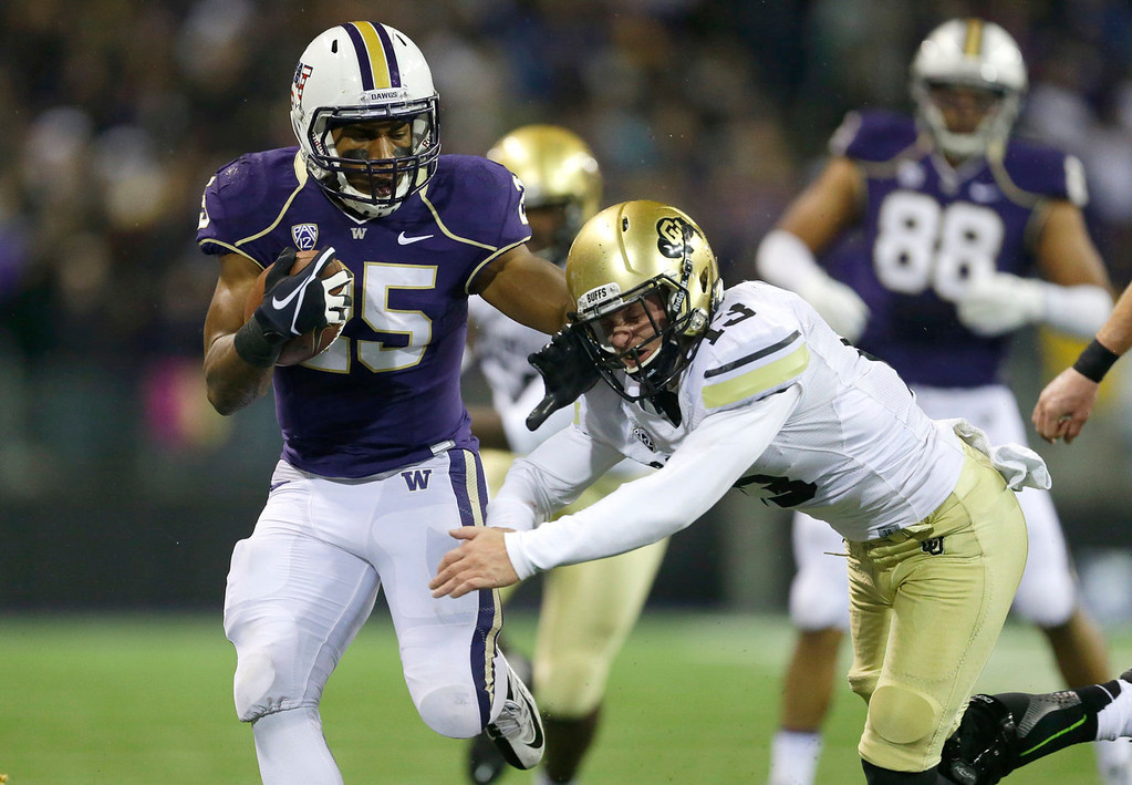 . Washington running back Bishop Sankey (25) pushes Colorado defensive back Parker Orms, right, out of the way in the first half of an NCAA college football game on Saturday, Nov. 9, 2013, in Seattle. (AP Photo/Ted S. Warren)