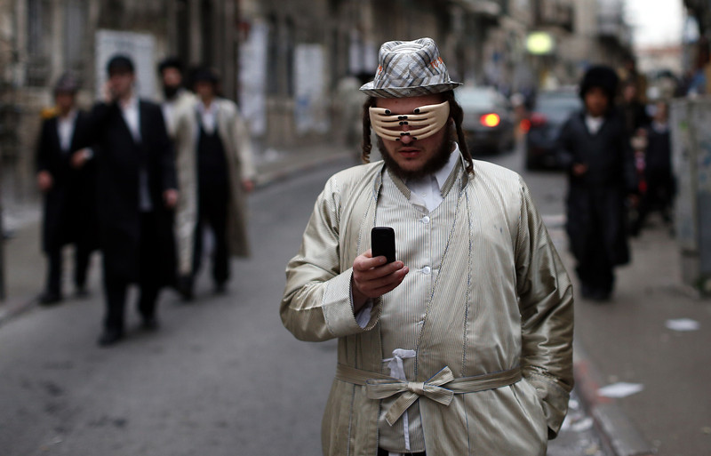 . An Ultra-Orthodox Jewish man wears a mask as he celebrates the Purim holiday in the ultra-orthodox Mea Shearim neighborhood in Jerusalem on March 17, 2014. The carnival-like Purim holiday is celebrated with parades and costume parties and drinking wine to commemorate the deliverance of the Jewish people from a plot to exterminate them in the ancient Persian empire 2,500 years ago, as recorded in the Biblical Book of Esther.  (THOMAS COEX/AFP/Getty Images)