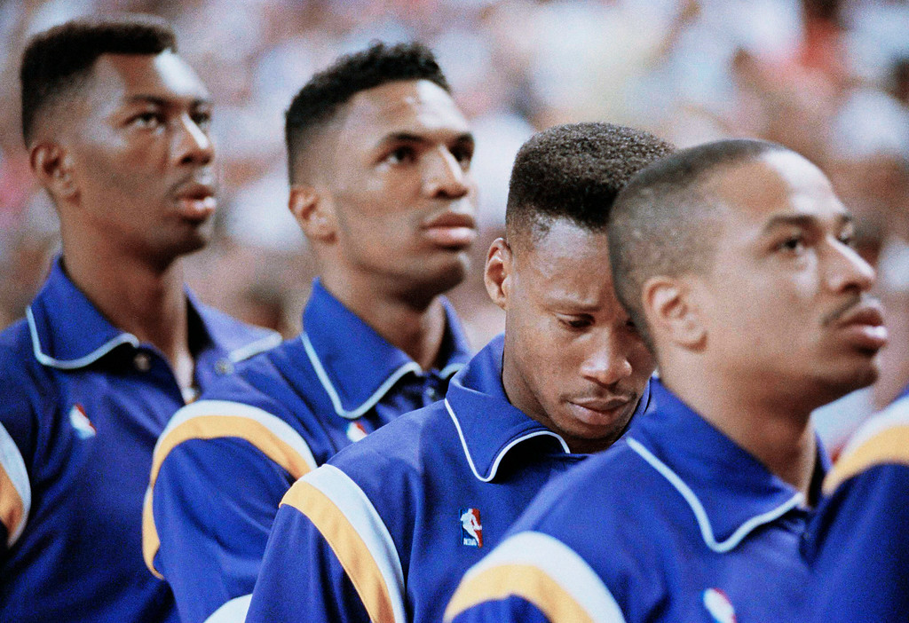 . Los Angeles Lakers guard Byron Scott, center, bows his head in emotion during the playing of the National Anthem before the start of their game against the Phoenix Suns, Nov. 8, 1991.  Lakers guard Larry Drew, right, and rookie Keith Owens join him as emotions run high during a prayer ceremony for retired Laker Magic Johnson, who announced he was HIV positive Thursday.  (AP Photo/Craig Fujii)