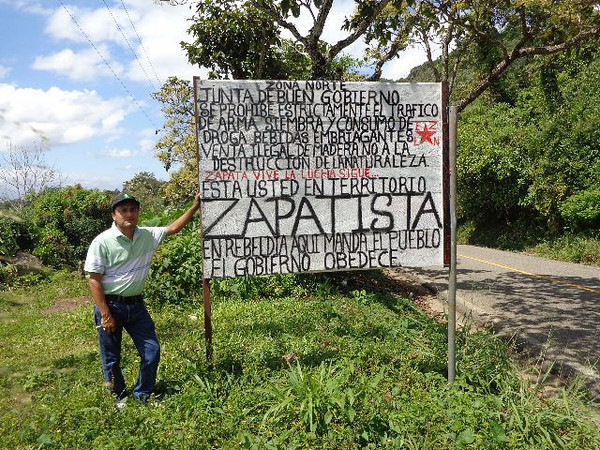 Jesus stands by a sign marking the entrance to a village between Palenque and Ocosingo governed by Zapatistas.
