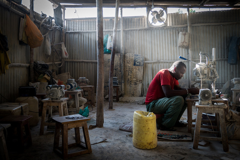 Grinding bone into jewelry in Kibera