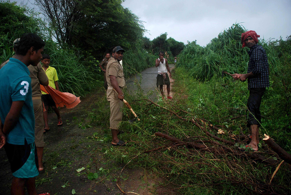 . Indian police force members and volunteers clear branches from the village road due to heavy cyclonic wind with rain in Badabandha Village near Gopalpur, about 195 kilometers south from eastern city Bhubaneswar on October 12, 2013.   Nearly half a million people have been evacuated from India\'s impoverished east coast ahead of a massive cyclone expected to make landfall on October 12 evening, disaster officials said. ASIT KUMAR/AFP/Getty Images