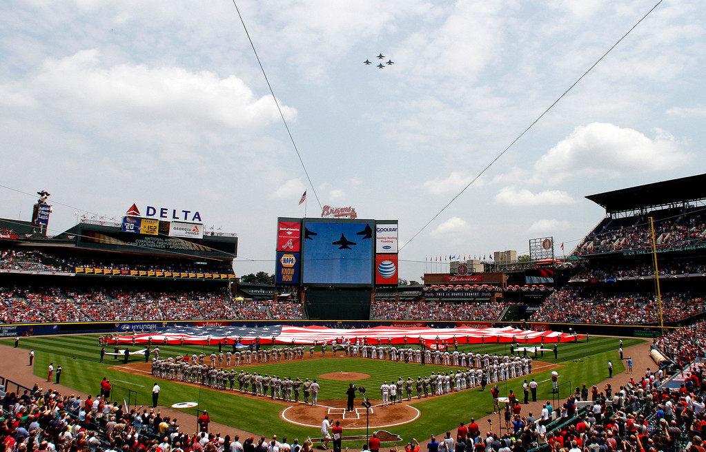 . Jets fly over as members of the U.S. Military hold the American Flag across the outfield, in honor of Memorial Day, before a baseball game between the Atlanta Braves and the Boston Red Sox on Monday, May 26, 2014, in Atlanta, Ga. (AP Photo/Butch Dill)