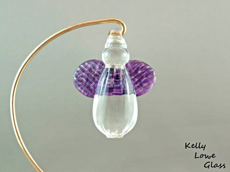 """Hanging Glass Angel - Purple  Height: Approx 8cm (3.15"""") Across the Wings: Approx 5.5cm (2.17"""") Depth: Approx 3cm (1.19"""") Weight: Approx 85g (0.19 lbs)  *Brass hanger in pictures is not included  Please note: as each piece begins its life as molten glass and is blown/sculpted by hand into the final product, individual pieces might have slight variations in size and/or appearance. Please rest assured however that the standard of quality is quite high, and no substandard pieces will be sold."""