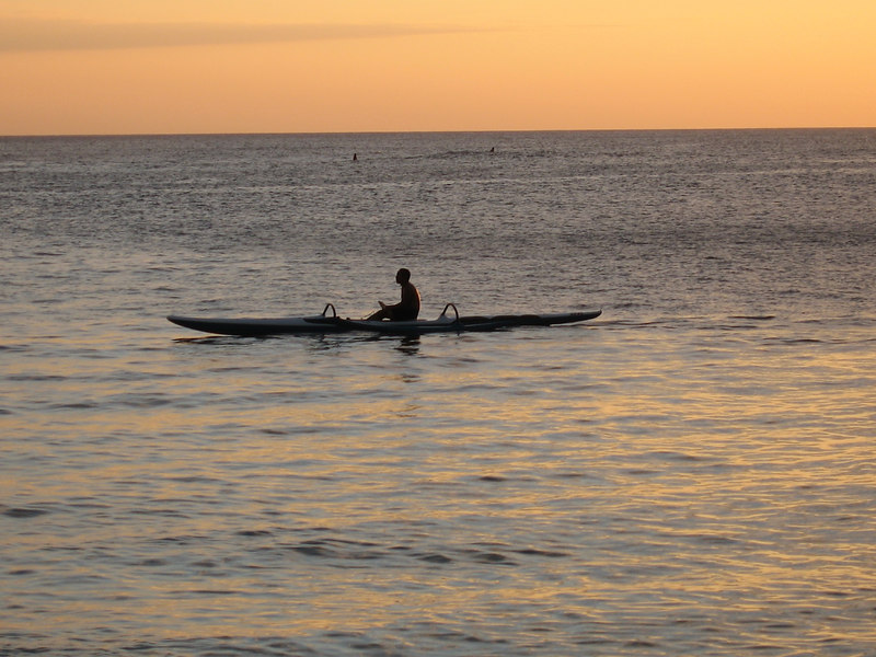 Young guy in an outrigger sitting in the suns path.