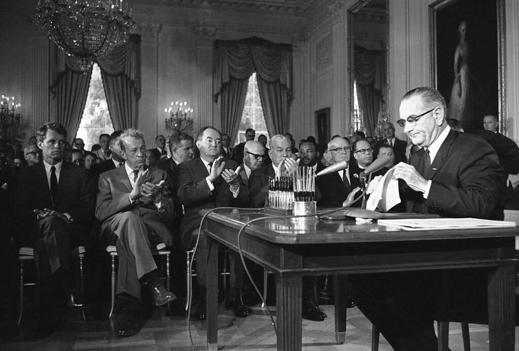 . President Lyndon B. Johnson is applauded as he finished his speech in the White House in Washington on July 2, 1964, over a radio-TV network prior to signing the 1964 Civil Rights Bill. Front row from left: Atty. Gen. Robert F. Kennedy, Sen. Everett M. Dirksen, R-Ill; Sen. Hubert H. Humphrey, D-Minn.; Rep. Charles Halleck, R-Ind.; and Rep. Emanuel Celler, D-N.Y. Second row: Whitney Young, behind Dirksen, executive director, National Urban League; Rep. Richard Bolling, D-Mo.; Dr. Martin Luther King, Southern Christian Leadership Conference; and Sen. Thomas H. Kuchel, R-California. (AP Photo)