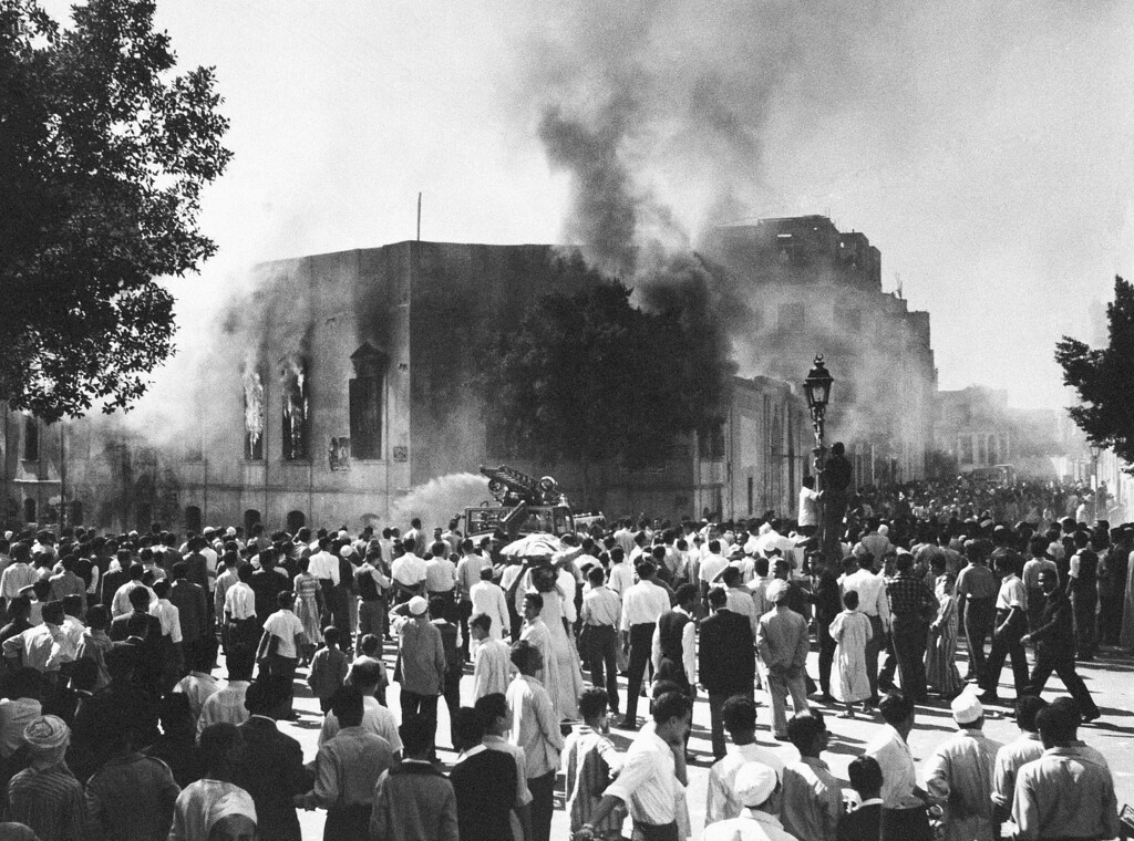 . A vengeful mob stand around the headquarters of the fanatic Muslim Brotherhood in Cairo, Egypt on Oct. 27, 1954, after putting it to the torch in retaliation against on October 26 attempted assassination of Premier Gamal Abdel Nasser in Alexandria. A Cairo announcement said that a Brotherhood member fired eight shots at Nasser. The arrest of 60 more Brotherhood members, including four of its supreme councilmen, also was announced. (AP Photo)