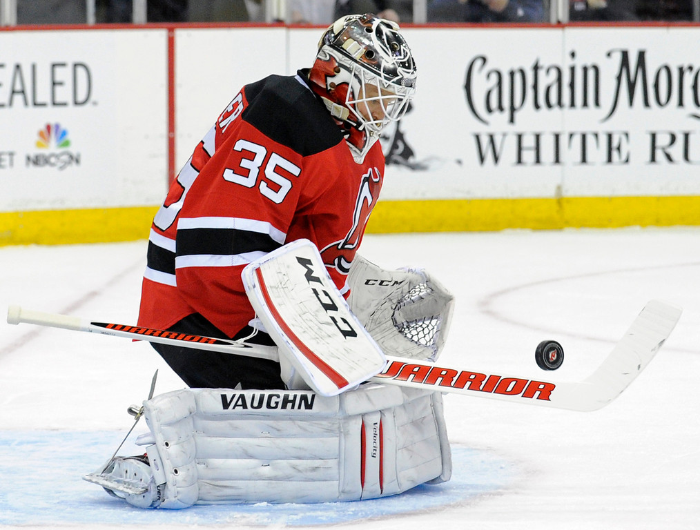 . New Jersey Devils goaltender Cory Schneider makes a save during the first period of an NHL hockey game against the Colorado Avalanche, Monday, Feb. 3, 2014, in Newark, N.J. (AP Photo/Bill Kostroun)